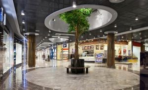 Black metal ceiling grille used in a shopping centre with circular cutouts for life size trees